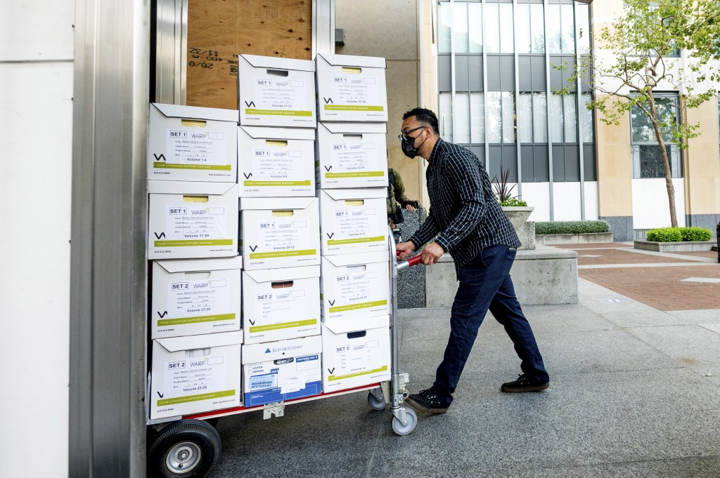 A member of Apple's legal team rolls exhibit boxes into the Ronald V. Dellums building in Oakland, Calif., as the company faces off in federal court a...
