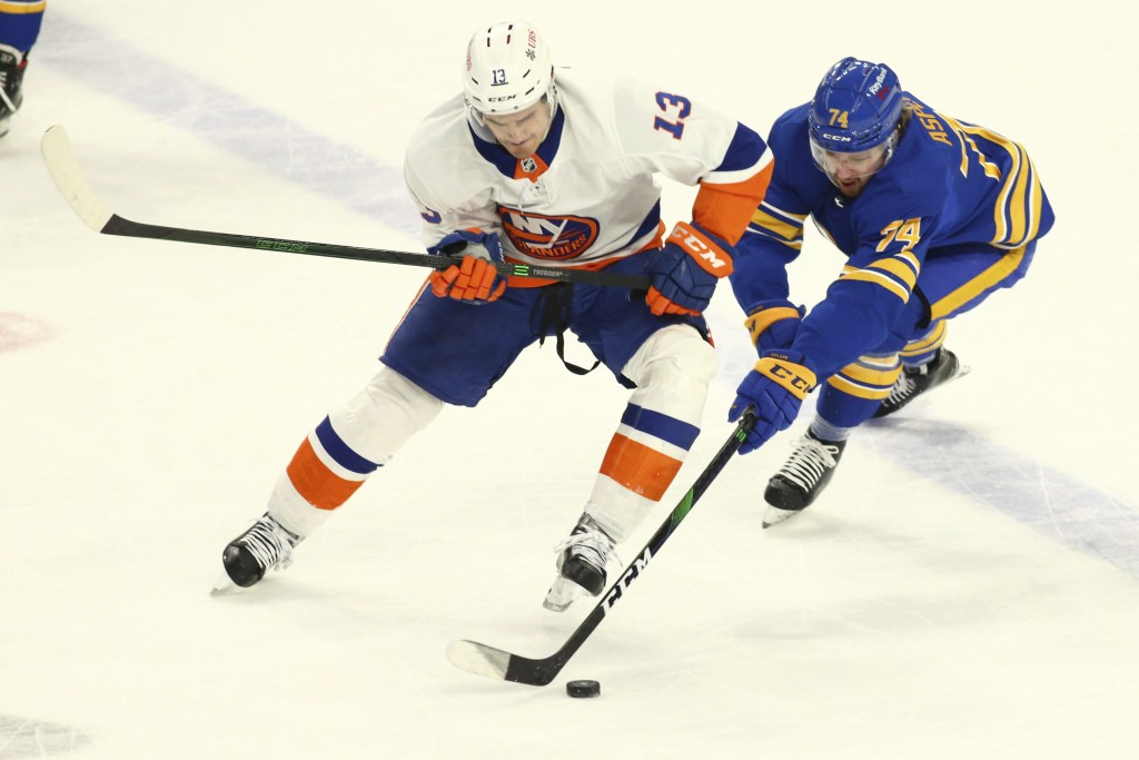 Buffalo Sabres forward Rasmus Asplund (74) losses the puck to New York Islanders forward Mathew Barzal (13) during the first period of an NHL hockey g...