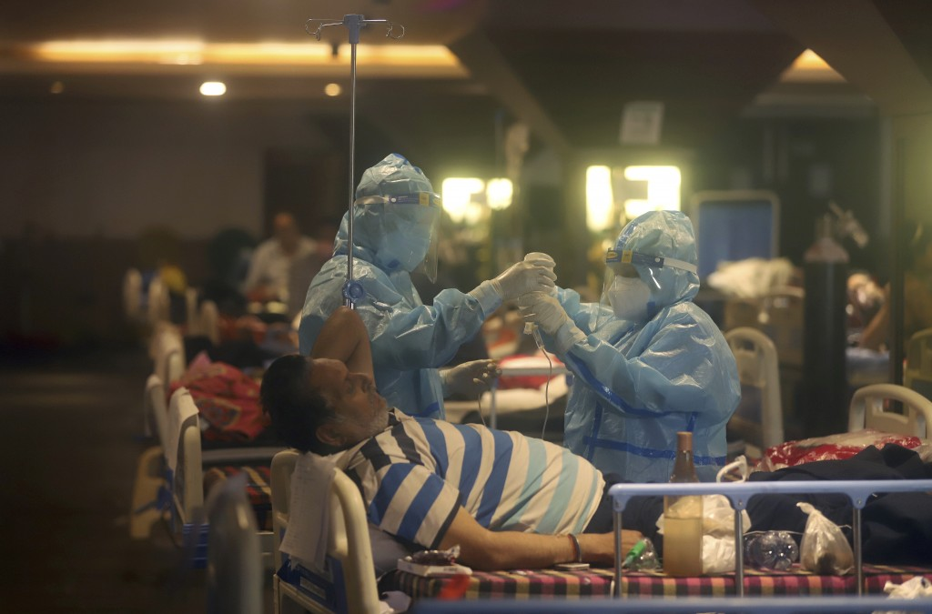 FILE - In this April 30, 2021, file photo, health workers attend to COVID-19 patients at a makeshift hospital in New Delhi, India. COVID-19 infections...