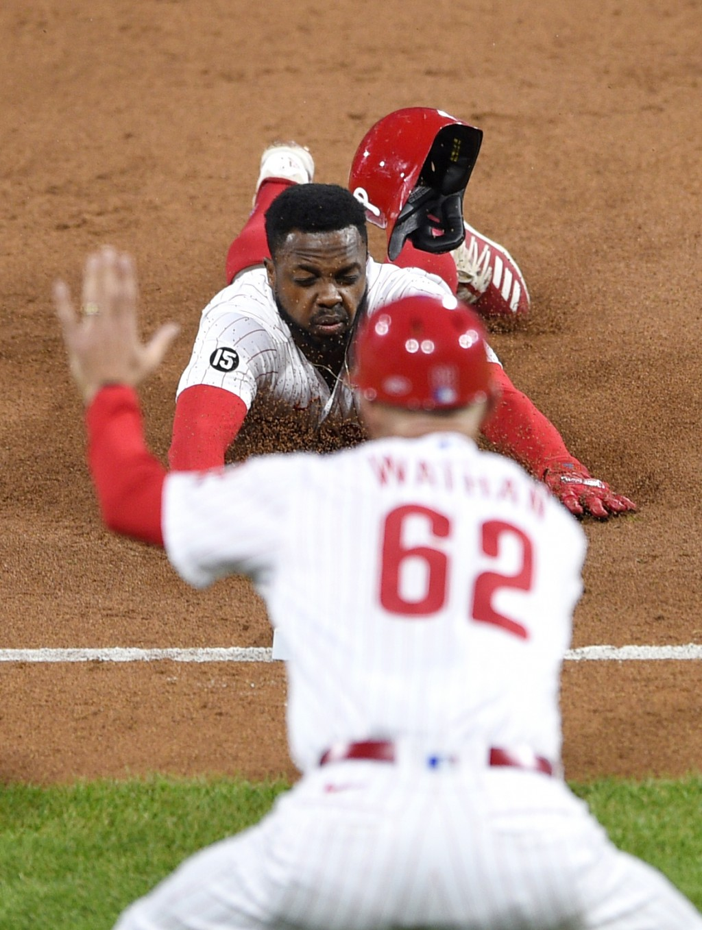 Philadelphia Phillies' Roman Quinn dives into third base safely as third-base coach Dusty Wathan (62) directs during the second inning of a baseball g...