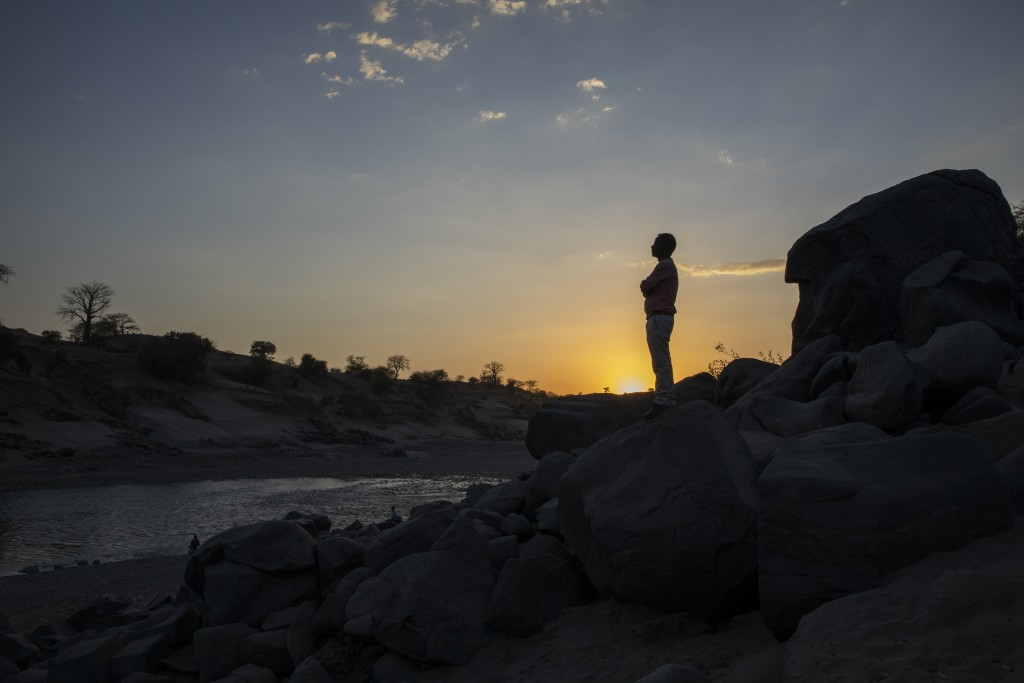 Surgeon and doctor-turned-refugee, Dr. Tewodros Tefera, stands at the Tezeke River crossing in Hamdayet, Sudan, on March 16, 2021. At left across the ...