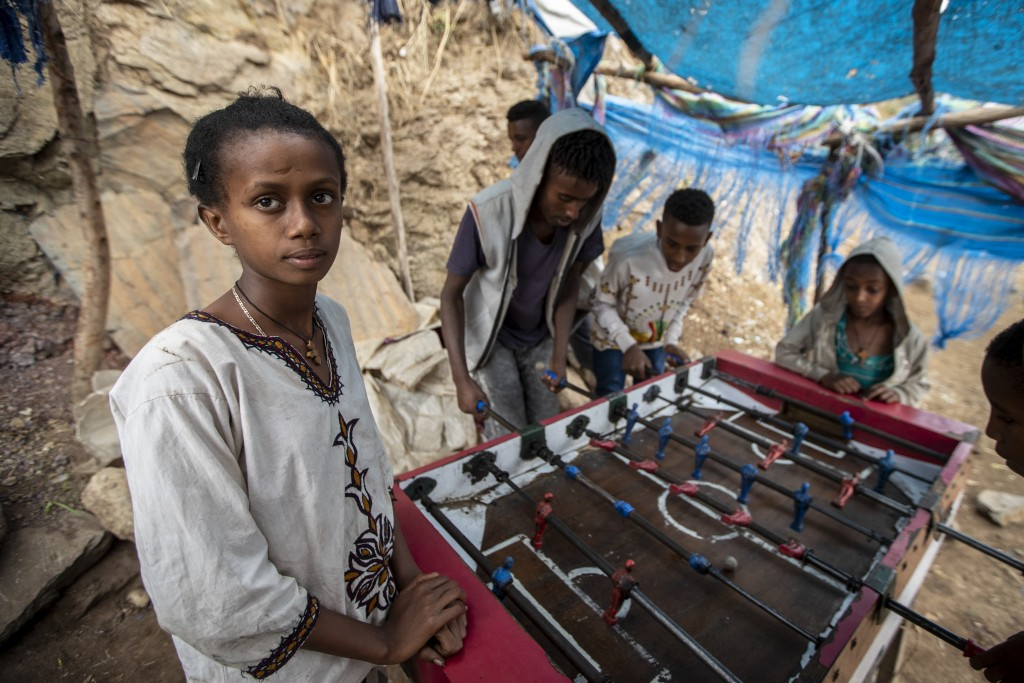 A girl watches while boys and young men play table football on the street, as Ethiopian Orthodox Christians celebrate Easter Sunday, in Gondar, in the...