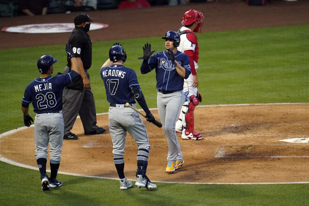 Tampa Bay Rays' Willy Adames, center right, is high-fived by Austin Meadows (17) after Adames scored on a single by Mike Brosseau during the third inn...