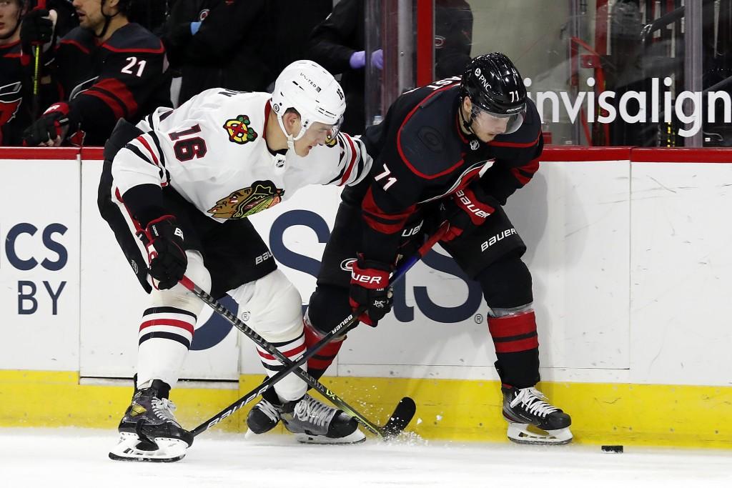 Carolina Hurricanes' Jesper Fast (71) and Chicago Blackhawks' Nikita Zadorov (16) battle along the boards during the second period of an NHL hockey ga...