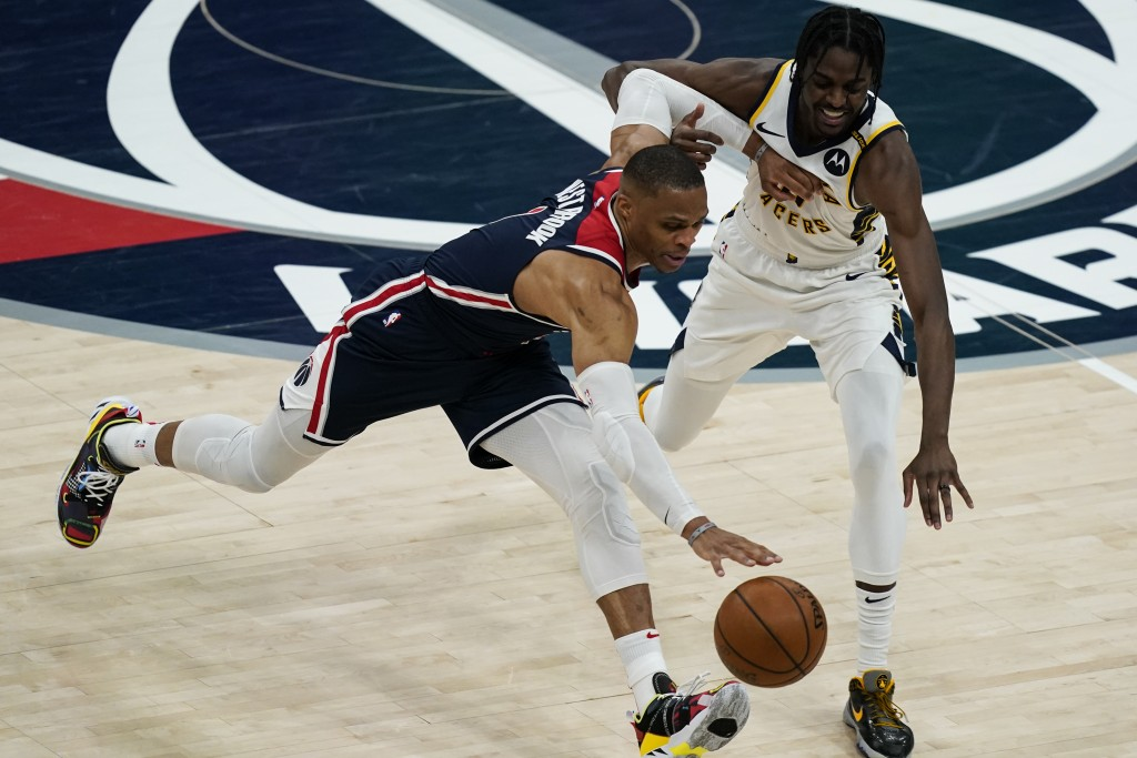 Washington Wizards guard Russell Westbrook (4) gets past Indiana Pacers guard Justin Holiday (8) during the second half of a basketball game, Monday, ...