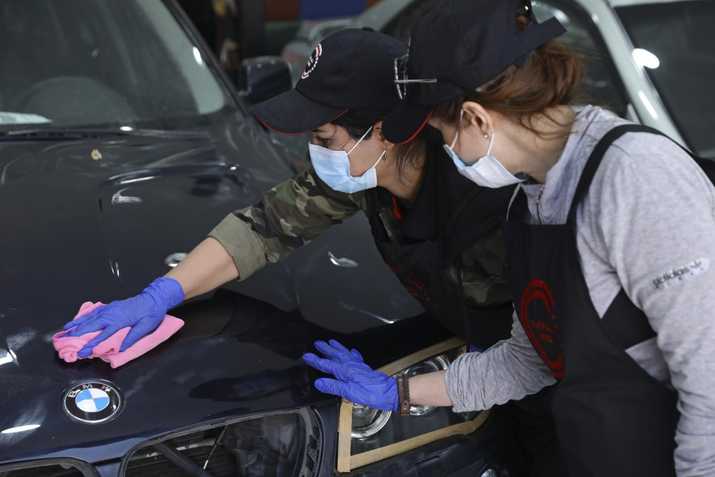 Female car detailer Maryam Roohani polishes a car as her trainee Farahnaz Deravi watches, at a detailing shop in Tehran, Iran, April 18, 2021. The aut...