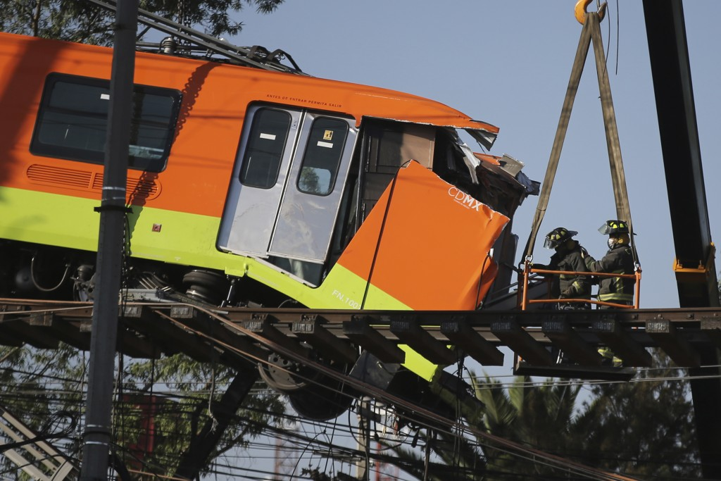 Firefighters work to lower to the ground a subway car dangling from a collapsed elevated section of the metro, in Mexico City, Tuesday, May 4, 2021. T...