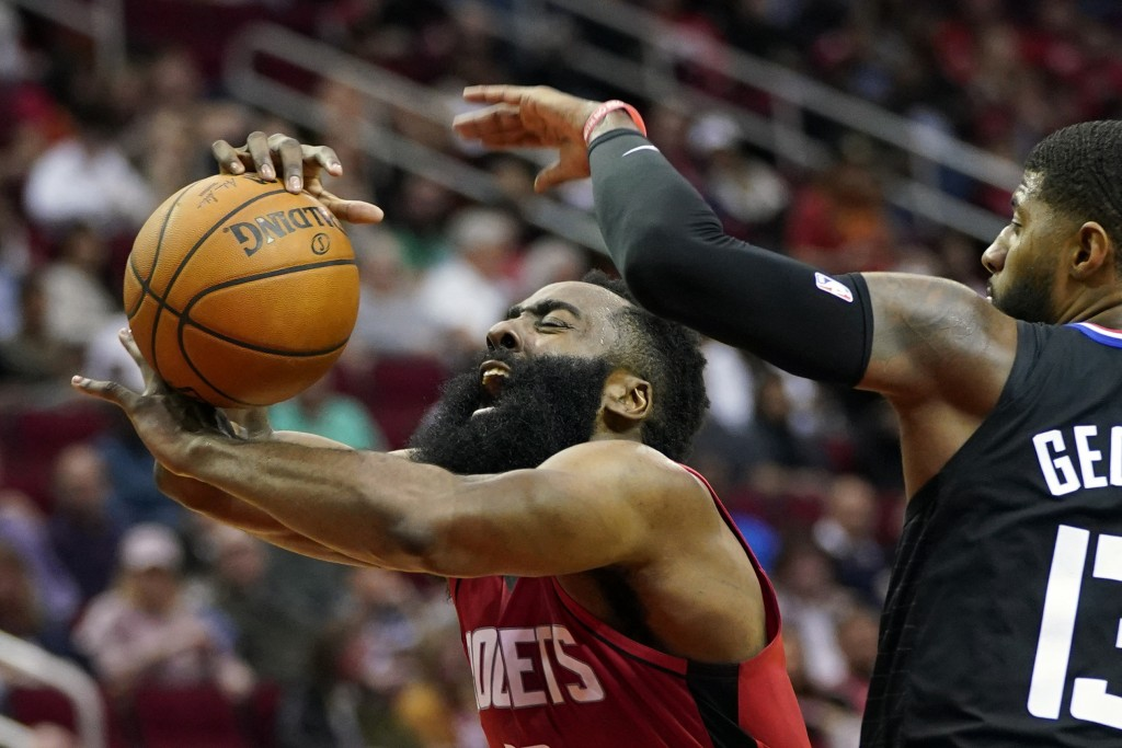 FILE - In this March 5, 2020, file photo, Houston Rockets' James Harden, left, is fouled by Los Angeles Clippers' Paul George during the second half o...