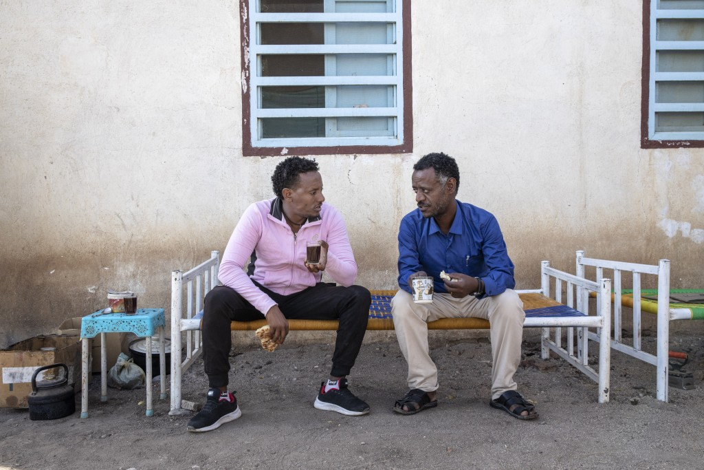 Surgeon and doctor-turned-refugee, Dr. Tewodros Tefera, right, drinks tea and eats breakfast with a friend before starting his workday, at the Sudanes...