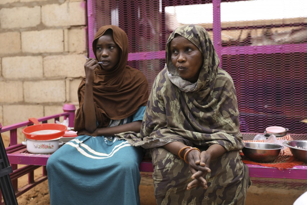 Saadia Ahmed, mother of the Sudanese migrant Mutawakel Ali, sits with her daughter at her home, in Khartoum, Sudan, Friday April 30, 2021. Ali narrowl...