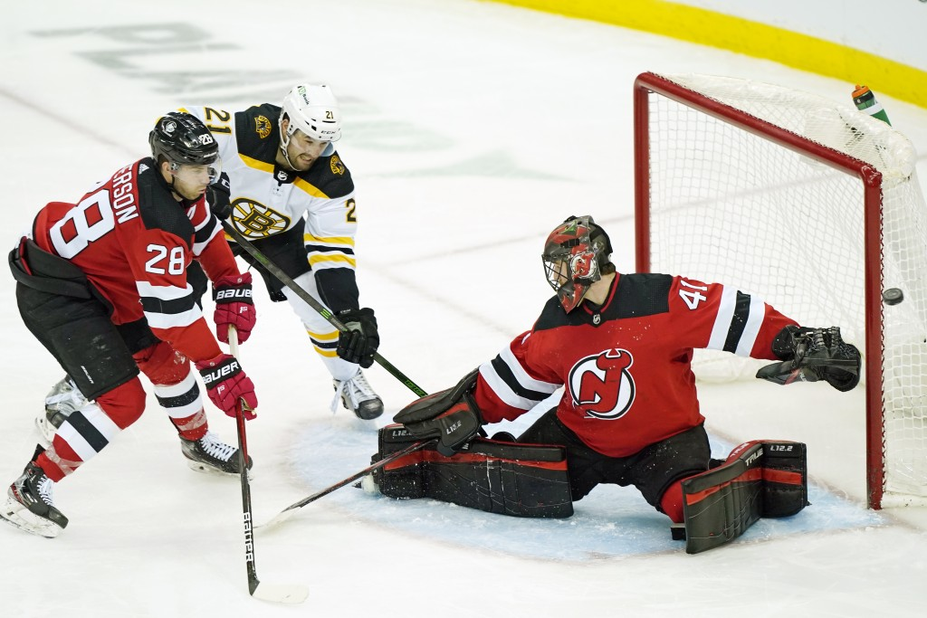 The puck sails wide of New Jersey Devils goaltender Scott Wedgewood (41) with Boston Bruins left wing Nick Ritchie (21) threatening as New Jersey Devi...