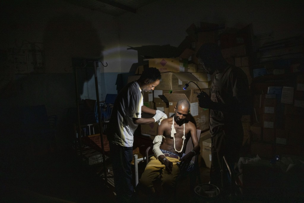 Surgeon and doctor-turned-refugee, Dr. Tewodros Tefera, cleans a wound and makes a cast for 31-year-old Tigrayan refugee Kalayu Hagos, who recently fl...