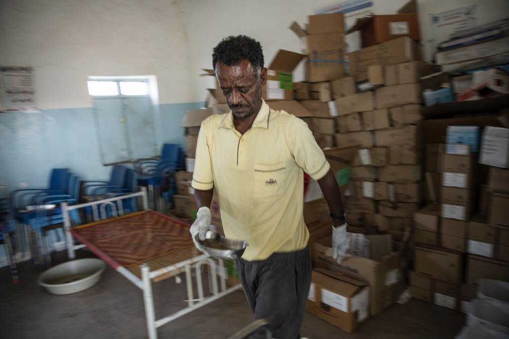 Surgeon and doctor-turned-refugee, Dr. Tewodros Tefera, sanitizes medical equipment, at the Sudanese Red Crescent clinic in Hamdayet, eastern Sudan, n...