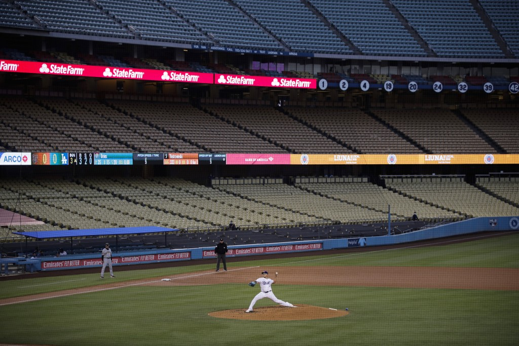 FILE - In this July 26, 2020, file photo, with the seats in Dodger Stadium empty, Los Angeles Dodgers starting pitcher Julio Urias throws the ball to ...