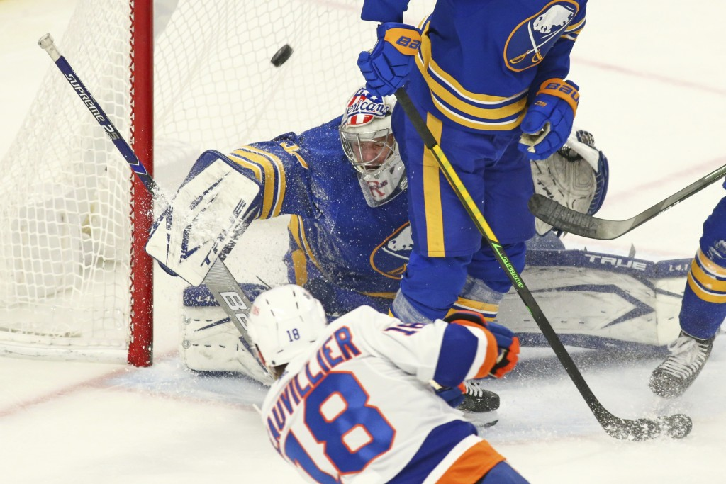 Buffalo Sabres goalie Michael Houser (32) stops New York Islanders forward Anthony Beauvollier (18) during the first period of an NHL hockey game, Mon...