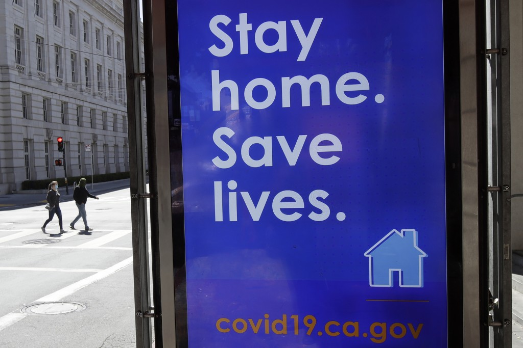 FILE - In this April 2, 2020, file photo, a sign advising people to stay home due to COVID-19 concerns is displayed at a MUNI bus stop in San Francisc...