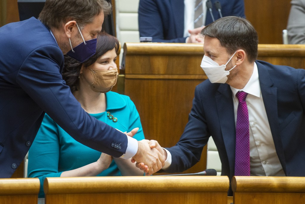Slovakia Prime Minister Eduard Heger, right, shakes hands with vice-premier and Minister of Finance Igor Matovic, left, and vice-premier Veronika Remi...