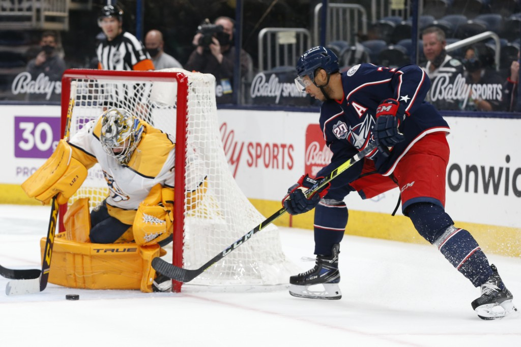 Nashville Predators' Juuse Saros, left, makes a save against Columbus Blue Jackets' Seth Jones during the second period of an NHL hockey game Monday, ...