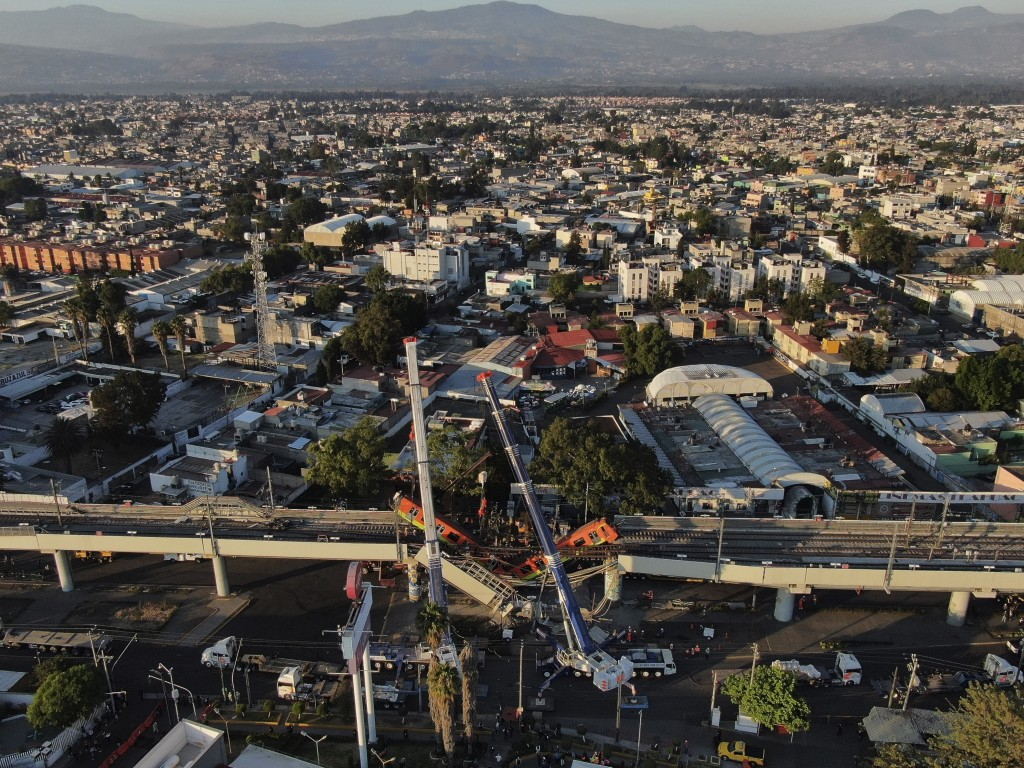 An aerial view of subway cars dangle at an angle from a collapsed elevated section of the metro, in Mexico City, Tuesday, May 4, 2021. The elevated se...