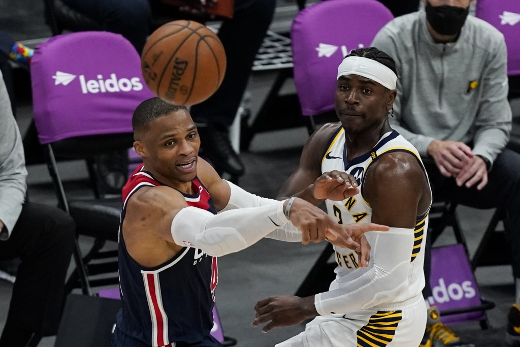 Washington Wizards guard Russell Westbrook (4) passes the ball as he is guarded by Indiana Pacers guard Aaron Holiday (3) during the second half of a ...