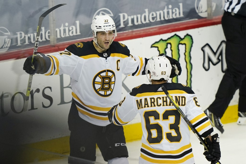 Boston Bruins center Patrice Bergeron (37) celebrates with left wing Brad Marchand (63) after scoring their second goal during the second period of an...