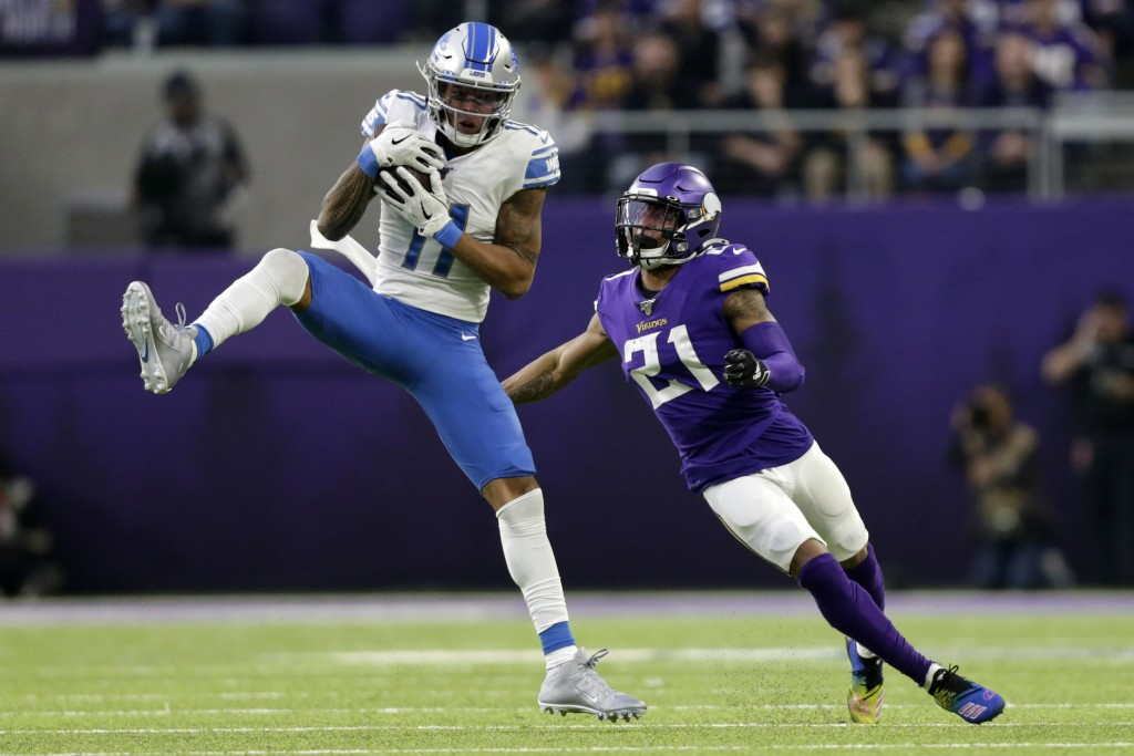 File-This Dec. 8, 2019, file photo shows Detroit Lions wide receiver Marvin Jones catching a pass ahead of Minnesota Vikings cornerback Mike Hughes, r...