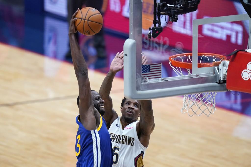 Golden State Warriors forward Draymond Green slam dunks against New Orleans Pelicans guard Eric Bledsoe (5) in the first half of an NBA basketball gam...