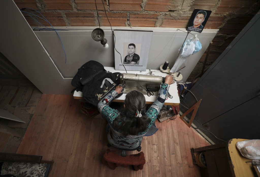 Doris Tejada, the mother of Oscar Alexander Morales, works at her home with a photo of her son who disappeared on New Year's eve 2007, next to her in ...