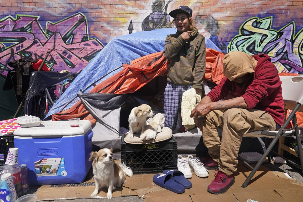 Lucio Lopez, left, talks with friends as he stands in a tent that is part of a homeless encampment in the Queens borough of New York, Tuesday, April 1...