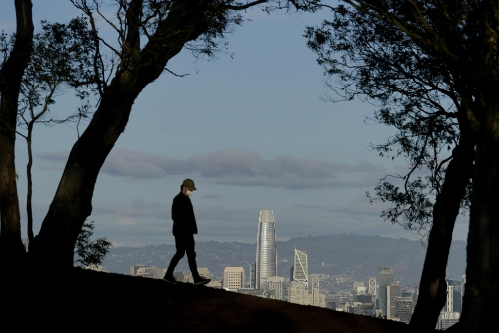 FILE - In this Dec. 17, 2020, file photo, a person wearing a face mask walks atop Tank Hill in front of the skyline during the coronavirus pandemic in...