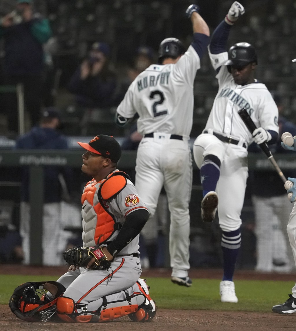 Baltimore Orioles catcher Pedro Severino kneels by the plate as Seattle Mariners' Tom Murphy (2) is greeted by Taylor Trammell, right, after Murphy hi...