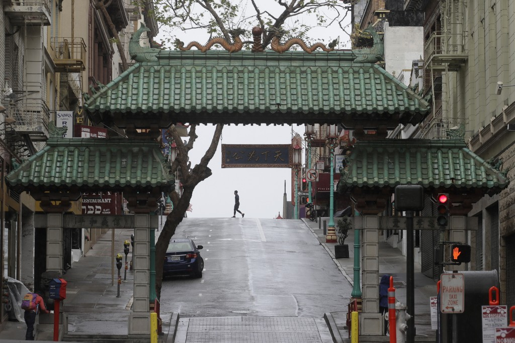 FILE - In this April 4, 2020, file photo, a pedestrian crosses Grant Street behind the Dragon Gate, an entrance to Chinatown in San Francisco. San Fra...
