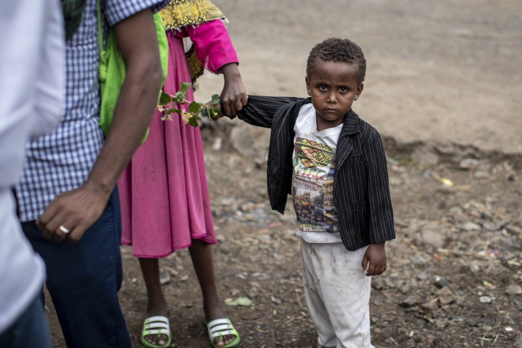 A young boy carries flowers as Ethiopian Orthodox Christians celebrate Easter Sunday in Gondar, in the Amhara region of Ethiopia Sunday, May 2, 2021. ...