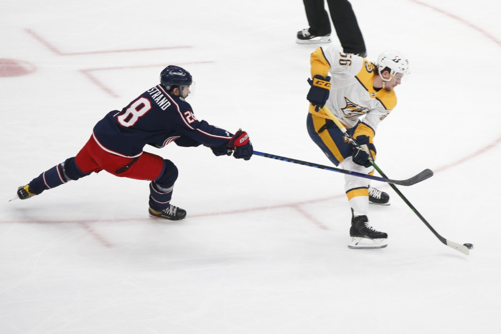 Columbus Blue Jackets Oliver Bjorkstrand, left, tries to stop Nashville Predators Erik Haula on a breakaway during the first period of an NHL hockey g...