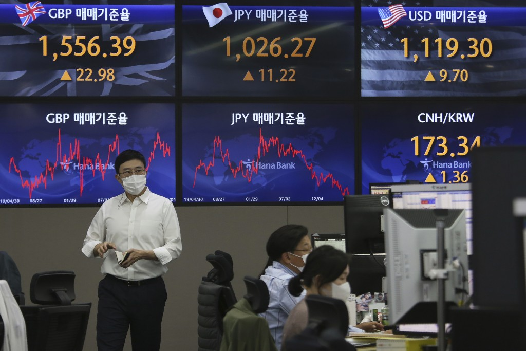 A currency trader passes by screens showing foreign exchange rates at the foreign exchange dealing room of the KEB Hana Bank headquarters in Seoul, So...