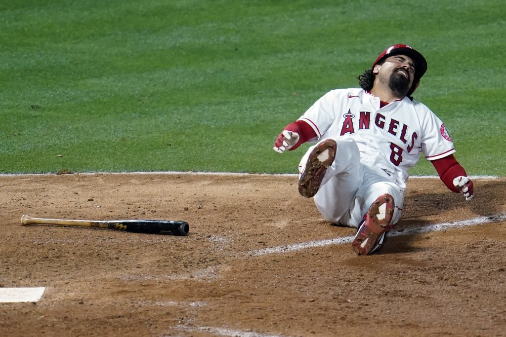 Los Angeles Angels' Anthony Rendon falls down after hitting a foul ball off his leg during the eighth inning of a baseball game against the Tampa Bay ...