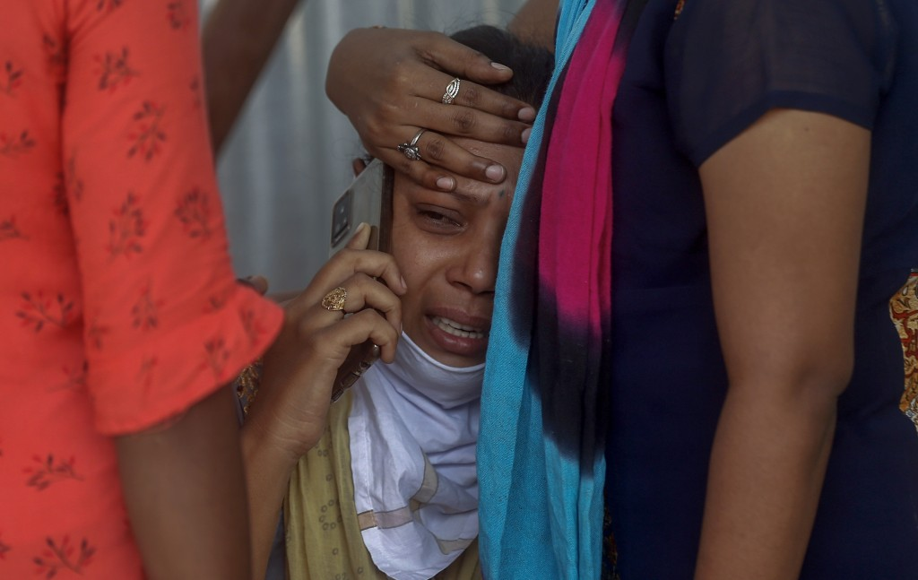 FILE - In this May. 3, 2021, file photo, relatives of a person who died of COVID-19 mourn outside a field hospital in Mumbai, India. COVID-19 infectio...