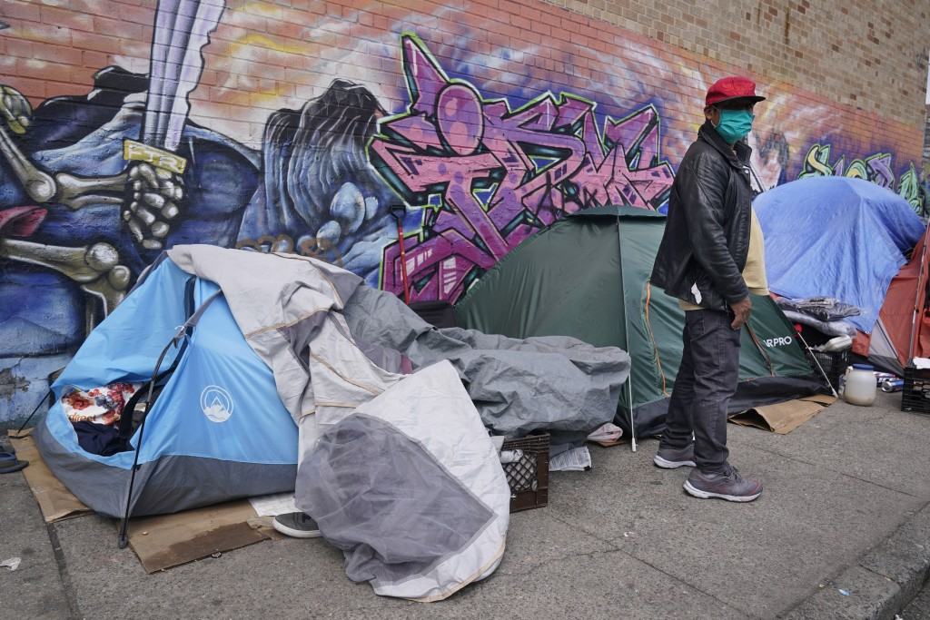 Sotero Cirilo stands near the tent, left, where he sleeps next to other homeless people in the Queens borough of New York, Wednesday, April 14, 2021. ...