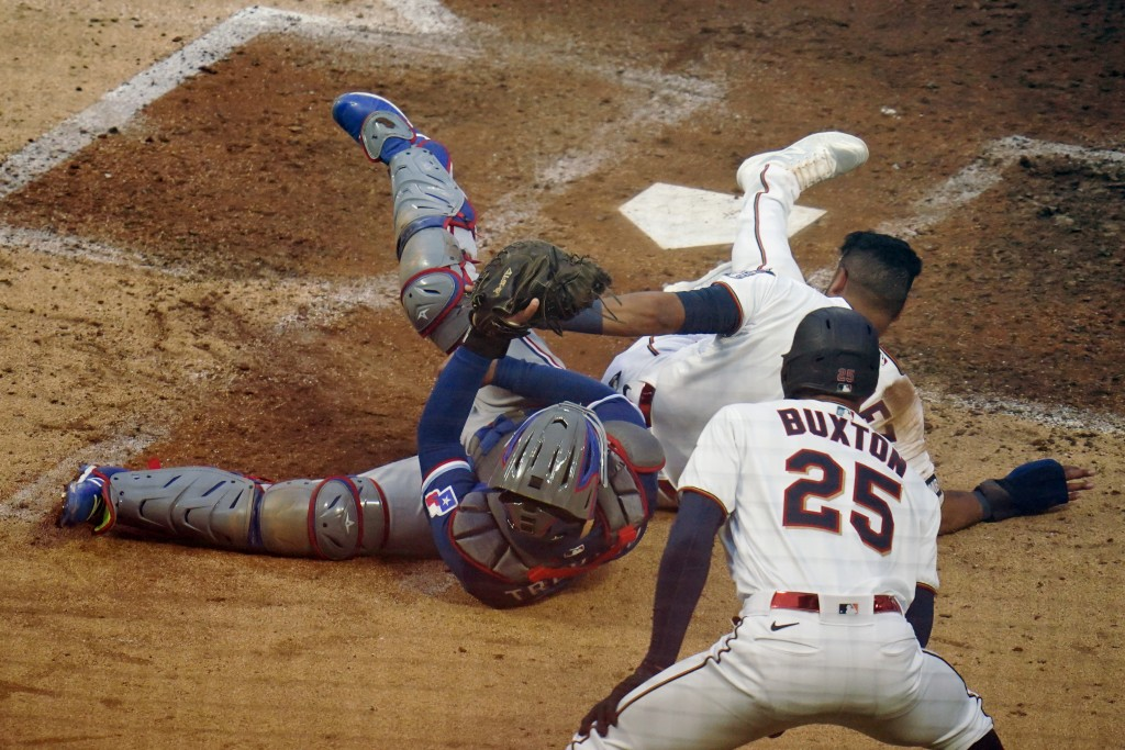 Minnesota Twins' Luis Arraez, top right, beats the tag by Texas Rangers catcher Jose Trevino, left, to score on a Josh Donaldson double in the third i...