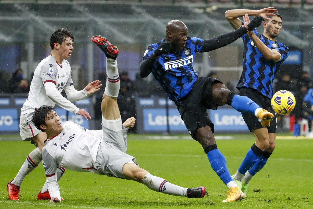 FILE - In this Dec. 5, 2020, file photo, Bologna's Takehiro Tomiyasu, left, and Inter Milan's Romelu Lukaku fight for the ball during a Series A socce...