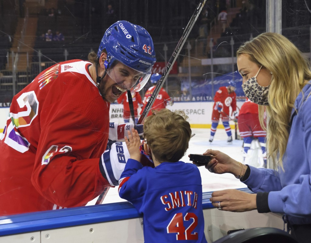 New York Rangers' Brendan Smith (42) says hello to his son Nolan and wife Samantha during warmups prior to an NHL hockey game against the Washington C...