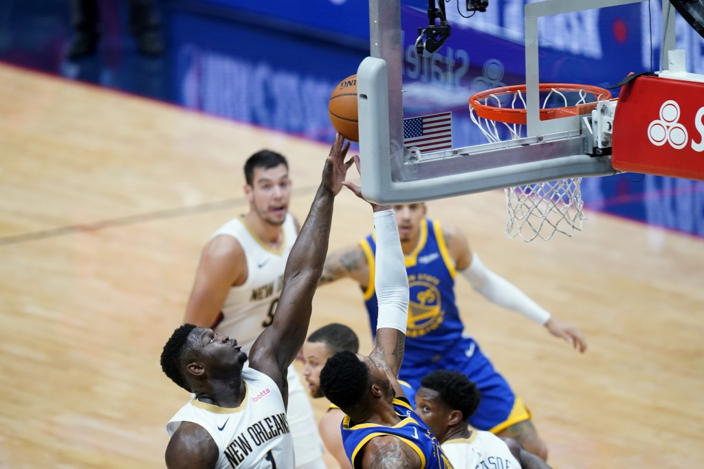 New Orleans Pelicans forward Zion Williamson (1) stops Golden State Warriors forward Kent Bazemore from reaching the basket in the first half of an NB...