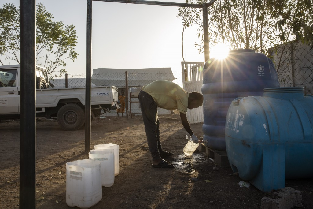 Surgeon and doctor-turned-refugee, Dr. Tewodros Tefera, fills a container with clean water to sanitize medical equipment, at the Sudanese Red Crescent...