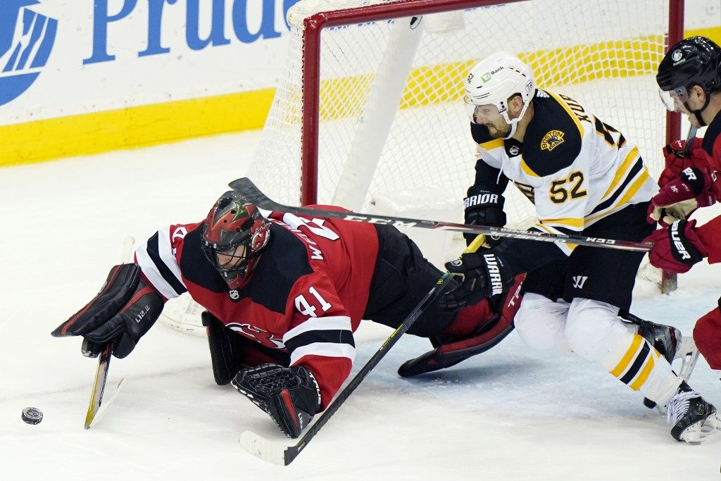 New Jersey Devils goaltender Scott Wedgewood (41) makes a save with Boston Bruins center Sean Kuraly (52) in front of the crease and Devils right wing...