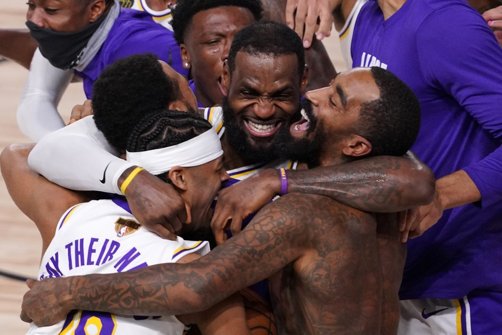 FILE - In this Oct. 11, 2020, file photo, Los Angeles Lakers' LeBron James (23) celebrates with his teammates after the Lakers defeated the Miami Heat...