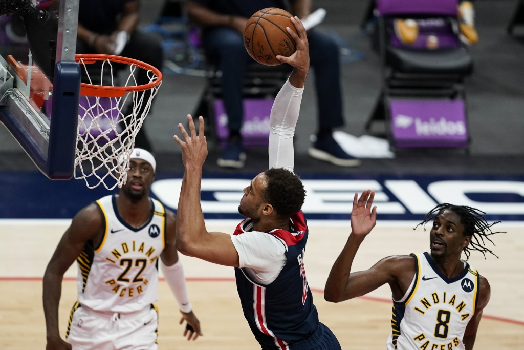 Washington Wizards forward Daniel Gafford (21) dunks the ball in front of Indiana Pacers guards Caris LeVert (22) and Justin Holiday (8) during the fi...