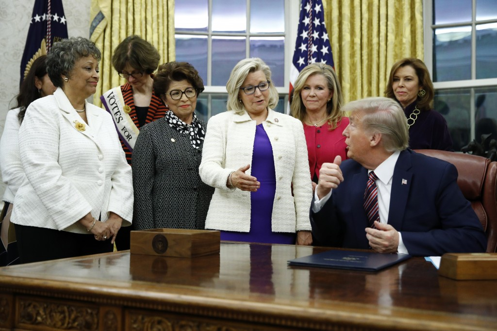 FILE - In this Nov. 25, 2019, file photo, Rep. Liz Cheney, R-Wyo., center, speaks with President Donald Trump during a bill signing ceremony for the W...