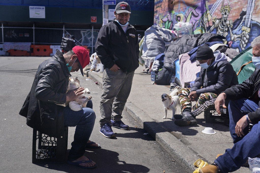 Sotero Cirilo, left, and Alfredo Martinez, second from left, relax in front of the tents where they have been sleeping in the Queens borough of New Yo...