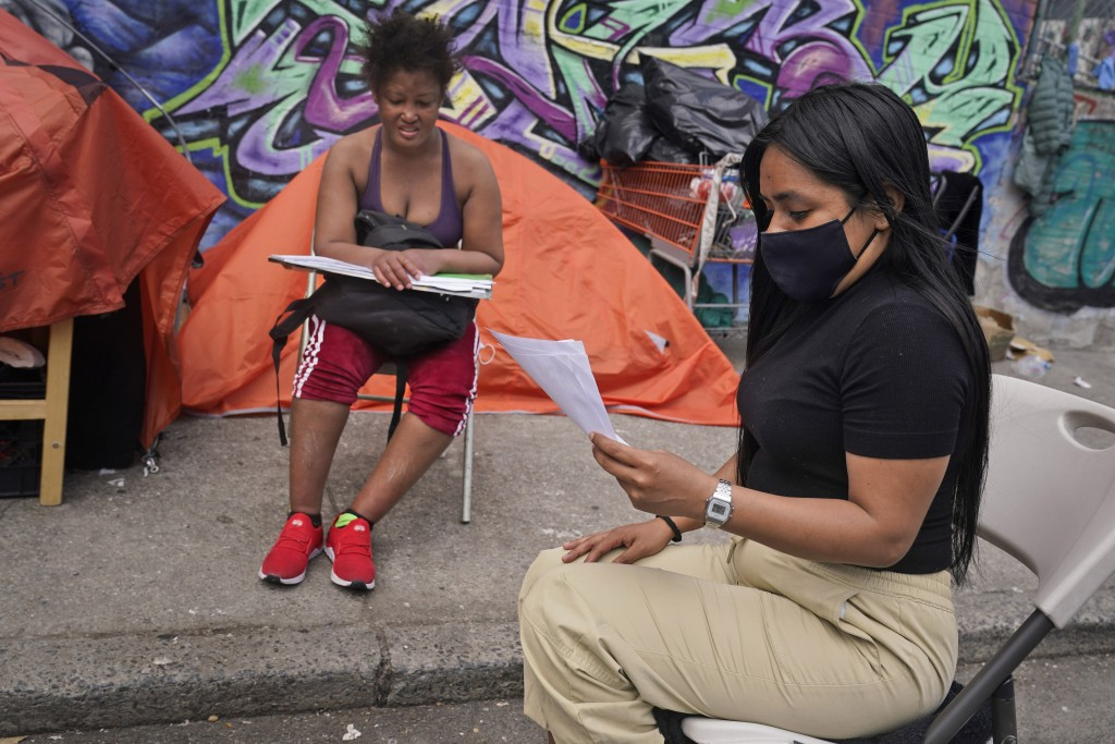 Yessenia Benitez, a 30-year-old licensed clinical social worker, tries to help a homeless woman sort through some documents near a homeless encampment...