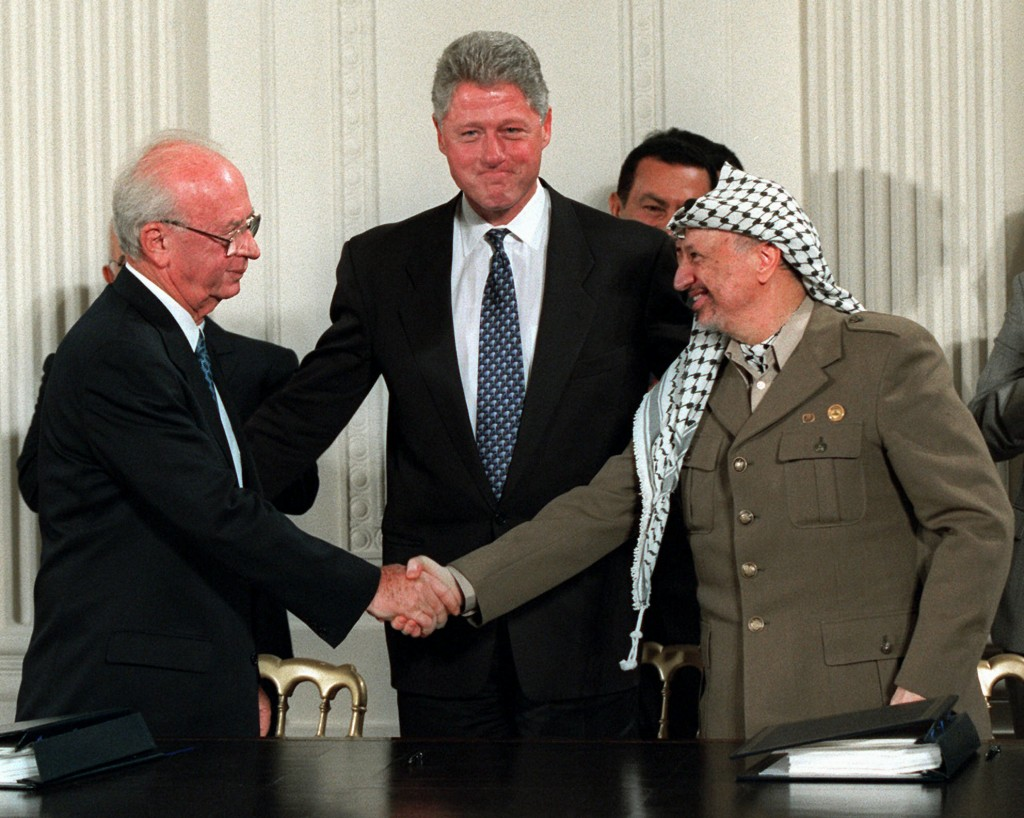 FILE - President Bill Clinton, center, looks on as Israeli Prime Minister Yitzhak Rabin, left, and PLO leader Yasser Arafat shake hands in the East Ro...